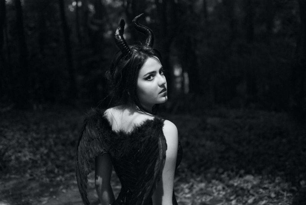 Black and white image of woman with horns and wings in forest.